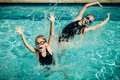 Two happy little girls playing in the swimming pool at day time Royalty Free Stock Photo