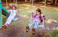 Two happy little girls swinging on the swing in a childrens playground Royalty Free Stock Photo