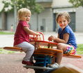Two happy little sisters on teetering board outdoor Royalty Free Stock Images