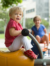 Two happy little sisters on teetering board outside Royalty Free Stock Photos