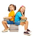 Two happy little years old girls asian caucasian sitting stack books their hand smiling standing isolated white Royalty Free Stock Photos