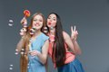 Two happy playful young women with colorful lollipop blowing bubbles