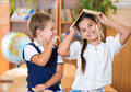 Two happy schoolchildren have fun in classroom at school Royalty Free Stock Photo