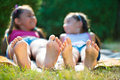 Two happy sisters lying on green grass outdoors in summer park Royalty Free Stock Photo