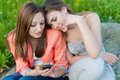 Two happy teenage girls reading message on mobile phone young women Royalty Free Stock Images
