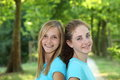 Two happy teenagers standing together in a park attractive teenage girls close back to back lush green looking at the camera with Royalty Free Stock Images