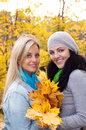 Two happy  women in autumn forest Stock Photo