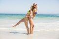 Two happy women in bikini and sunglasses having fun on the beach Royalty Free Stock Photo