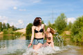 Two happy women having fun at lake in summer they wearing swimwear Stock Photos