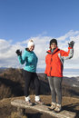 Two happy women hikers waving hello outdoors smiling sportive in the mountains with blue cloudy sky in background Stock Photography
