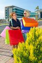 Two happy women out shopping stop to chat elderly in town at the side of a street with their brightly coloured bags in Stock Photography