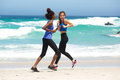Two happy women running on the beach Royalty Free Stock Photo
