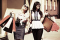 Two happy fashion women with shopping bags walking in city street Royalty Free Stock Photo