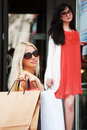 Two happy women shopping young with bags against a mall doorway Stock Photography