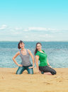 Two happy women sitting on the beach Royalty Free Stock Photo