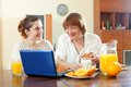 Two happy women using laptop during breakfast mature mother and daughter at home Stock Images