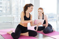 Two happy  women using tablet sitting in yoga studio Royalty Free Stock Photo