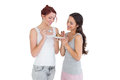 Two happy young female friends eating pastry together over white background Stock Photos