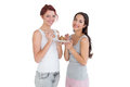 Two happy young female friends eating pastry together portrait of over white background Royalty Free Stock Image