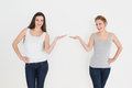 Two happy young female friends holding out their hands against white background Royalty Free Stock Photo