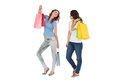 Two happy young female friends with shopping bags full length of over white background Stock Photo