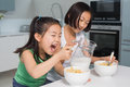 Two happy young girls eating cereals in kitchen the at home Royalty Free Stock Image