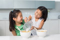 Two happy young girls pouring milk in bowl in kitchen the at home Stock Image