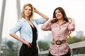 Two happy young women on the bridge standing Royalty Free Stock Photo