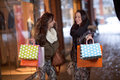 Two happy young women holding colorful shopping bags front stores Royalty Free Stock Image