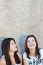 Two happy young women looking up on copy space teen girls Stock Image