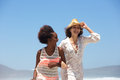 Two happy young women walking at the beach together Royalty Free Stock Photo