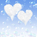 Two heart cloud clouds on a blue background with soap bubbles Stock Image