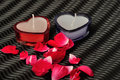 Two heart shape candles and red rose petals Royalty Free Stock Photo