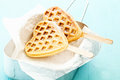 Two heart shaped belgian waffles on a stick inside tin can paper wrap sprinkled with cinnamon and sugar Stock Photo