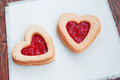 Two heart shaped cookies with jam close up Stock Images