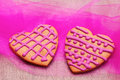Two heart shaped gingerbread cookies on pink fabric Stock Images
