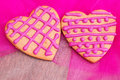 Two heart shaped gingerbread cookies on pink fabric Stock Photo