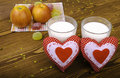 Two hearts apples on a napkin and two glasses of milk wooden background Royalty Free Stock Images