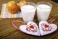 Two hearts apples on a napkin and two glasses of milk wooden background Royalty Free Stock Photos