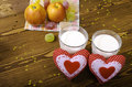 Two hearts apples on a napkin and two glasses of milk wooden background Stock Photos