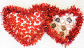 Two hearts with candy red tinsel hears surround mints chocolates and small Royalty Free Stock Photos