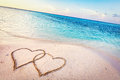 Two hearts drawn on sand of a tropical beach at sunset. Royalty Free Stock Photo