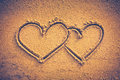 Two hearts handwritten on seashore sand. Vignette and vintage to Royalty Free Stock Photo