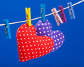 Two hearts hanging on a clothesline with clothespins Royalty Free Stock Photos