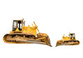 Two heavy dirty building bulldozers of yellow color: big and small, isolated. Royalty Free Stock Photo