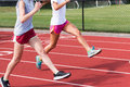 Two high school girls do running drills on a red track Royalty Free Stock Photo