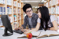 Two high school students studying together portrait of cheerful doing schoolwork in the library Stock Images