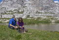 Two hikers by the alpine lake young having rest and studying map Royalty Free Stock Photography