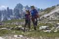 Two hikers in the mountains young on a mountain trail looking one direction Stock Photo