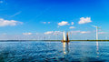 Two Historic Wooden Botter Boats in Full Sail near a Wind Farm along the Shore of Veluwemeer Royalty Free Stock Photo